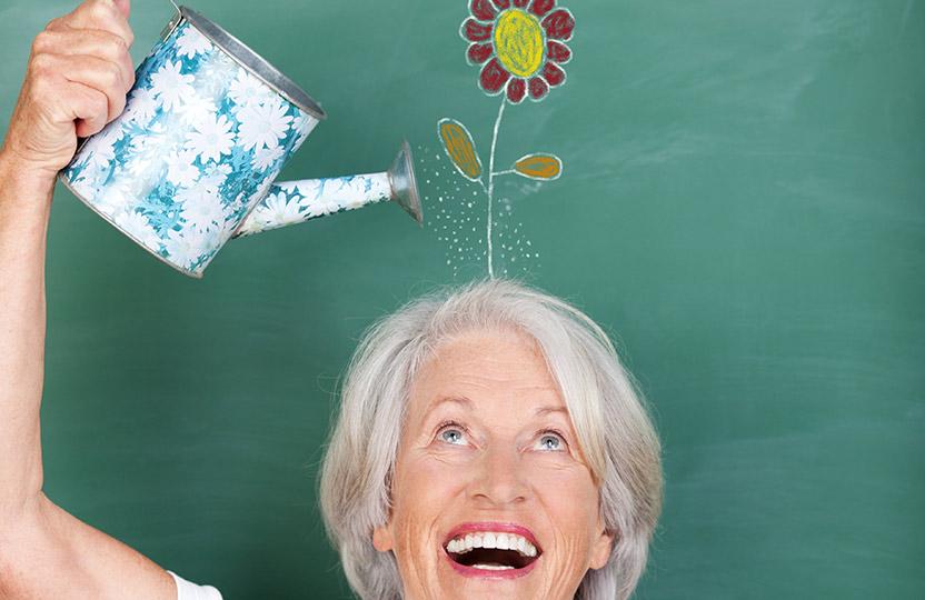 Lächelnde Seniorin gießt eine gemalte Blume über ihrem Kopf