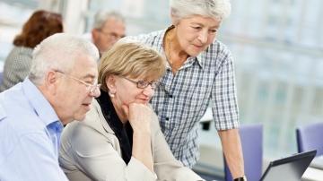 Ältere Menschen schauen auf einen Laptop