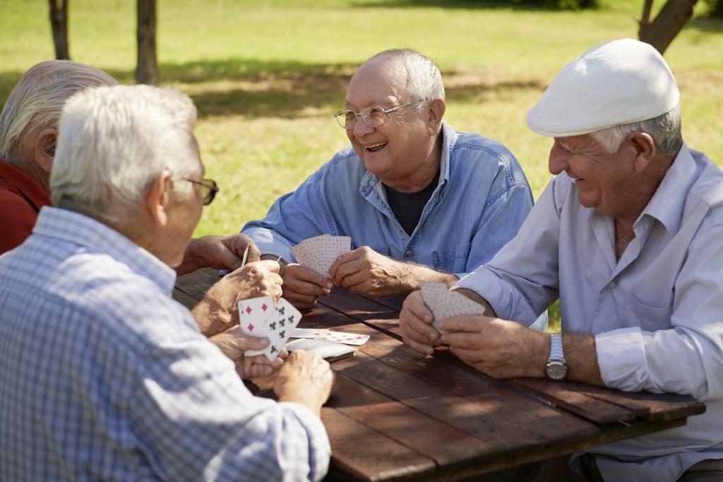 Aktive Freizeit des Ruhestandes: Gruppe von vier älteren Männern, die Spaß haben und Karten spielen im Park.