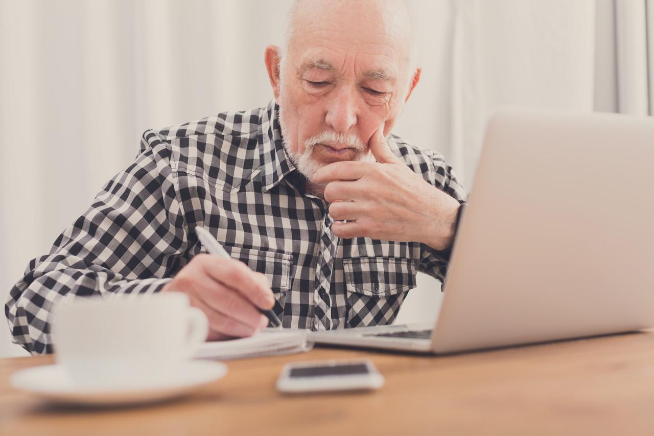 Ein älterer Mann schreibt etwas auf. Vor ihm ein Laptop und Smartphone.