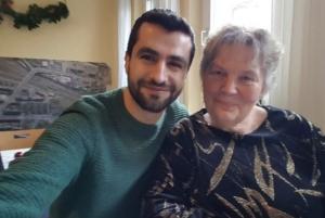 Ein Geflüchteter und eine ältere Frau lächeln in die Kamera.