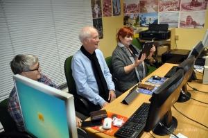 Sie sehen drei Seniorinnen und Senioren vor PCs.
