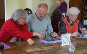 Eine Betreuerin ist mit einem Bewohnter einer Demenz-WG mit dem Tablet  beschäftigt.