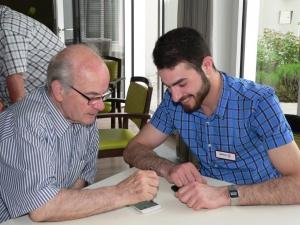 Ein ehrenamtlicher Mitarbeiter im Smartphone Café zeigt einem älteren Herren Anwendungen auf seinem Smartphone