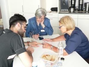 Ein ehrenamtlicher Mitarbeiter im Smartphone Café zeigt zwei Besucherinnen Anwendungen auf ihrem Smartphone