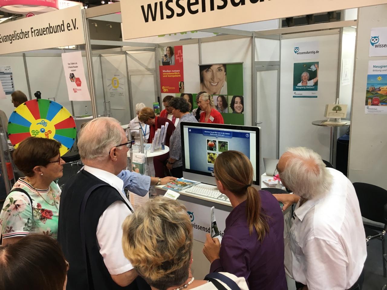Mehrere Personen schauen auf einen Bildschirm, auf dem Doppeltixx gezeigt wird.
