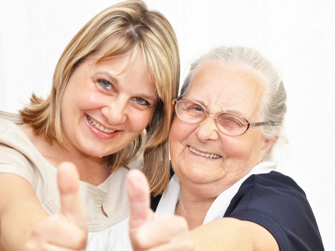 Eie jüngere und eine ältere Frau stehen nahe nebeneinander und machen gemeinsam eine ermutigende Daumen hoch Geste.