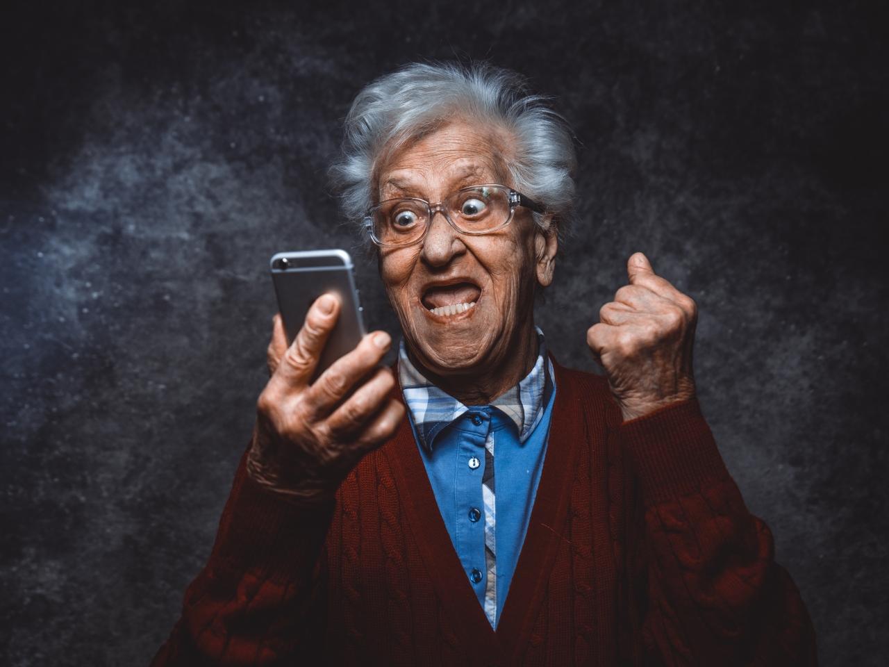 Man sieht einen älteren Mann, der jubelnd auf sein Smartphone schaut