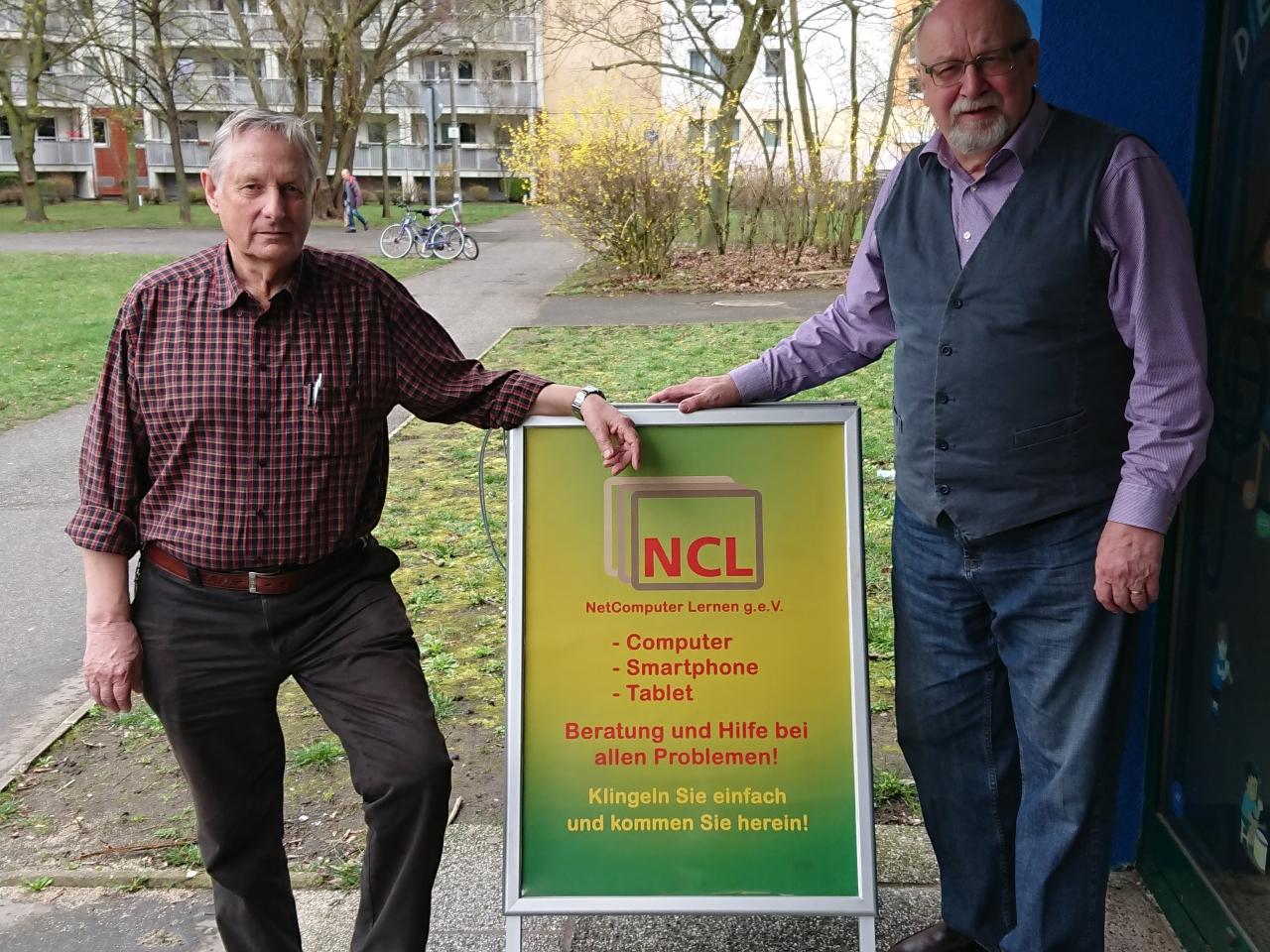 Zwei Männer mit dem Schild von NET Computer Lernen