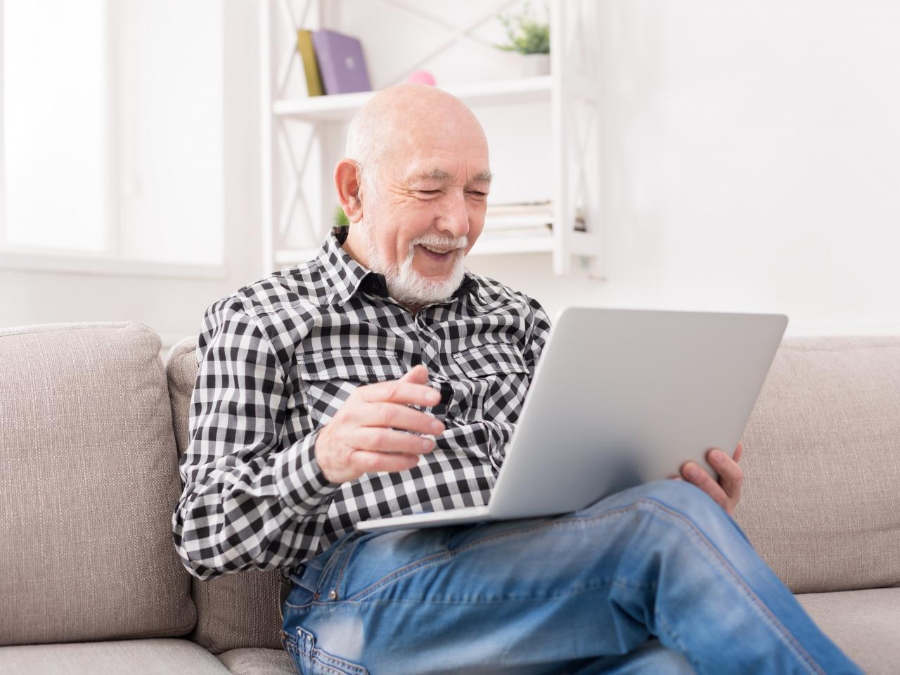 Auf dem Foto sieht man einen Mann, der mit einem Laptop auf dem Schoß auf einem Sofa sitzt