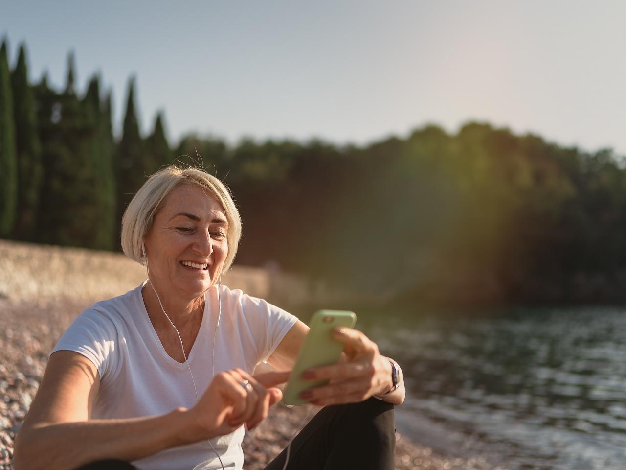 Eine Frau sitzt mit ihrem Smartphone am See