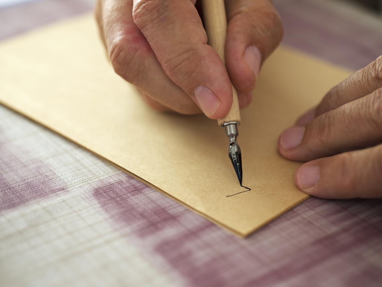Hand, eines älteren Mannes, die mit einer Feder einen Brief schreibt