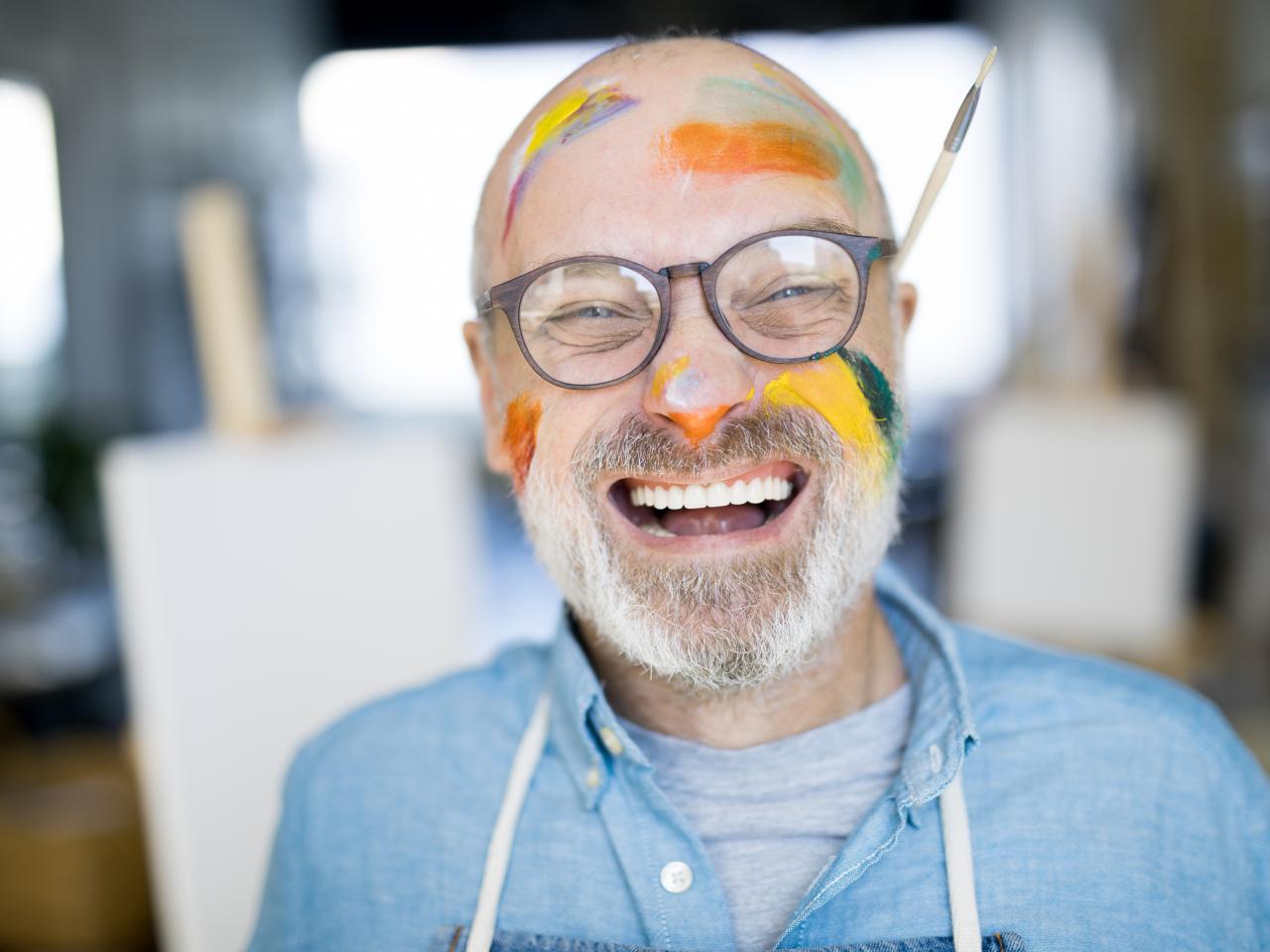 Lachender, älterer Mann mit Pinselstrichen im Gesicht