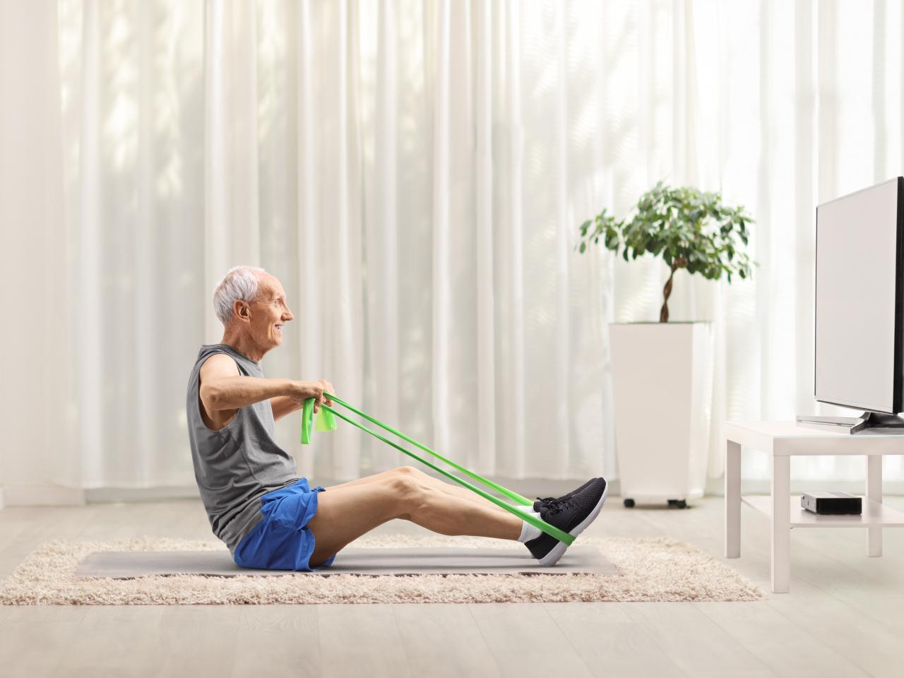 Älterer Mann macht Sport vor dem Fernseher