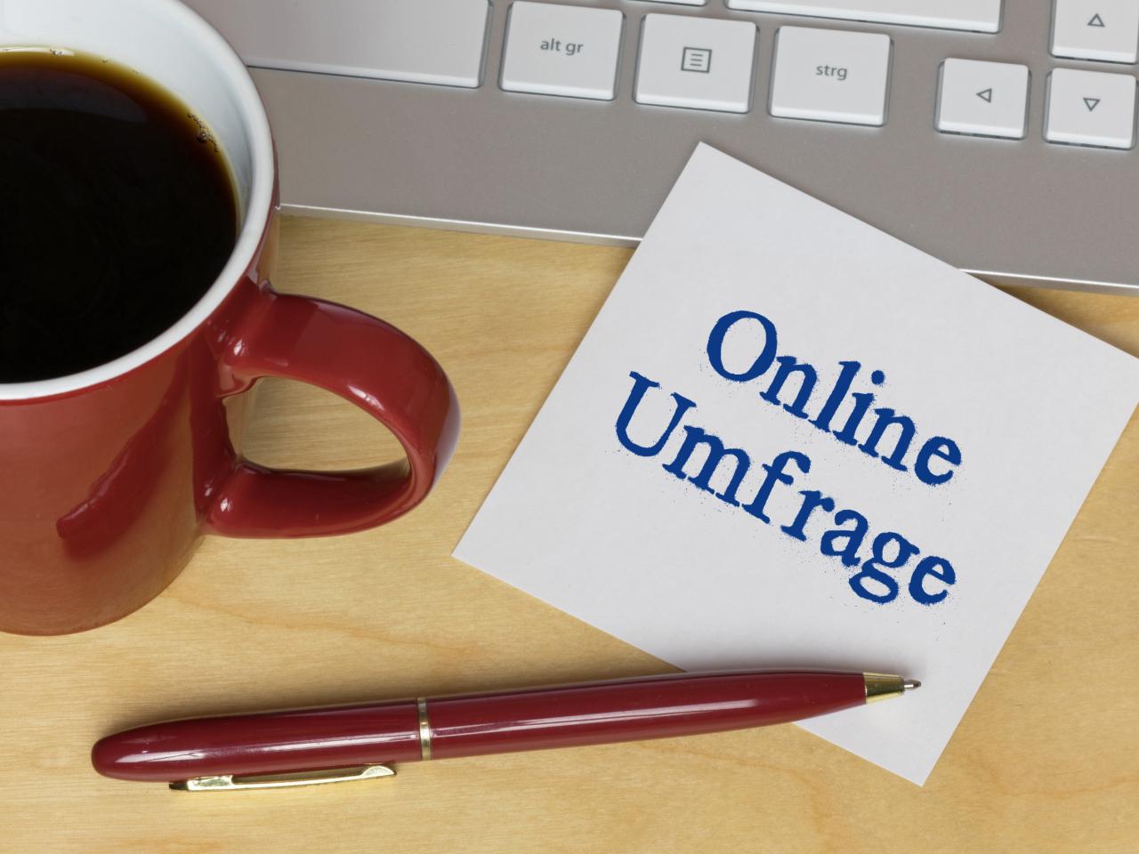 """Laptop, Kaffeetasse und Notizzettel """"Online Umfrage"""""""