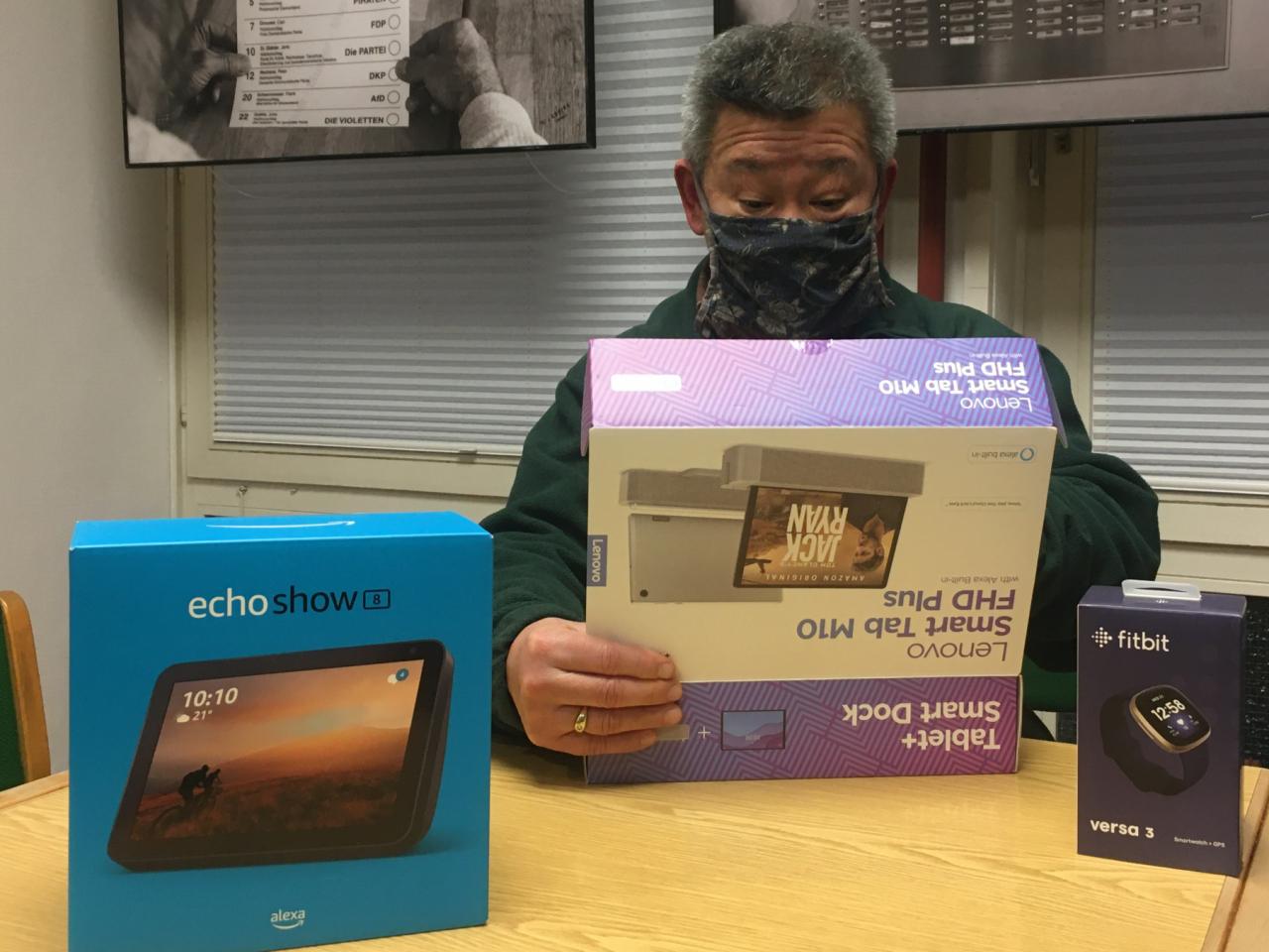 Mann packt ein Tablet aus einem Karton