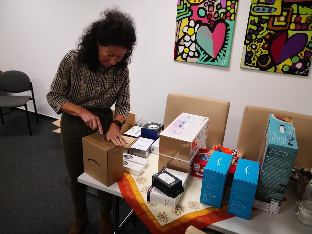 Frau packt eins von vielen Paketen mit Technik aus