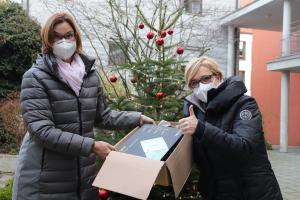 Zwei Frauen halten vor einem Weihnachtsbaum ein Paket