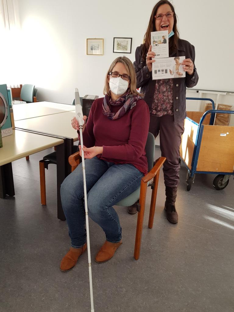 Zwei Frauen präsentieren eine Gehilfe für Sehbeeinträchtigte und ein EKG-Messgerät