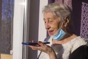 Ältere Frau spricht in ein Smartphone