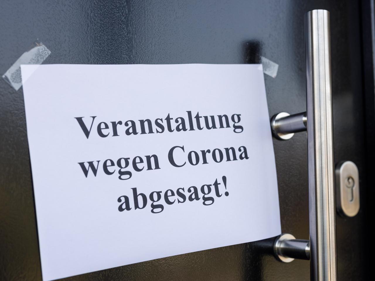 Zettel mit Veranstaltungsabsage wegen Corona auf einer Tür