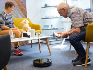 Ein jüngerer Mann erklärt einem älteren einen Staubsaugerroboter