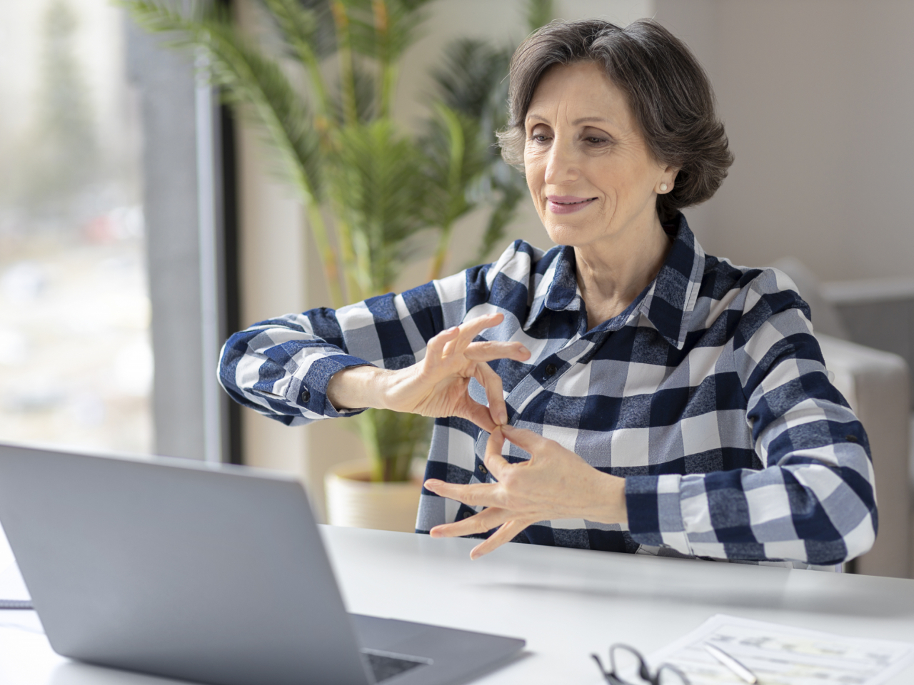 Deaf elderly woman uses sign language while video call using laptop while sitting in home office